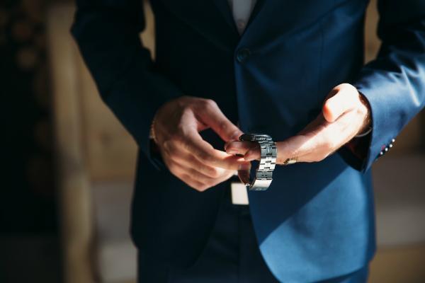 Mann im blauen Jackett mit Armbanduhr