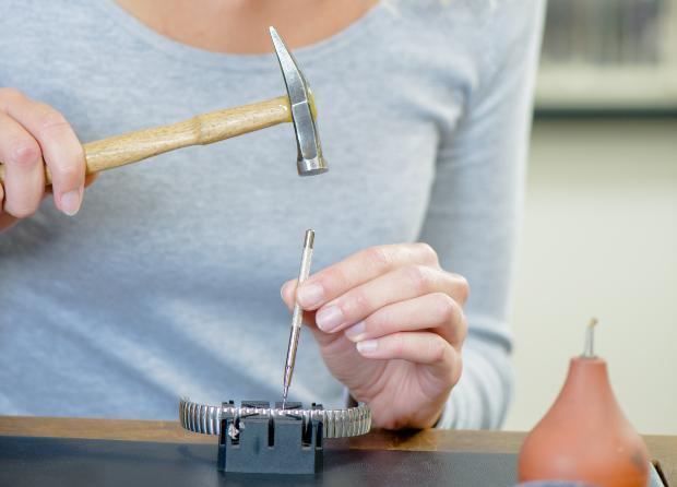 Frau benutzt Werkzeug für Armbanduhranpassung