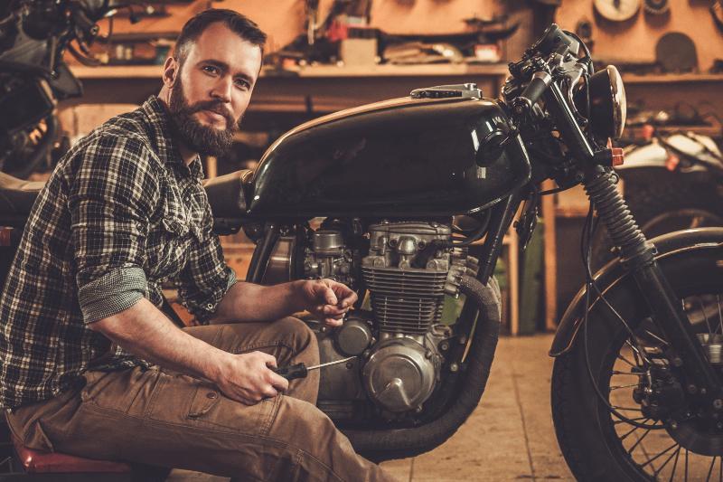 Ein Mann schraubt an einem schweren Vintage-Motorrad Breitling Zorro