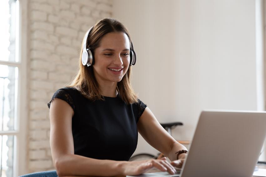 Junge Frau lernt mit Headset am Laptop - FHH Academy