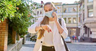 Frau schaut während Pandemie auf Armbanduhr