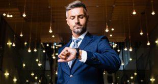 Eleganter Herr schaut auf Armbanduhr