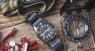 Armbanduhr liegt neben Kompass